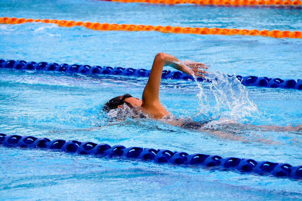 A boy swims in a pool between lane markers.